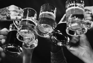 C'est une photo en noir et blanc de mains trinquant avec des chopes de bières remplies.