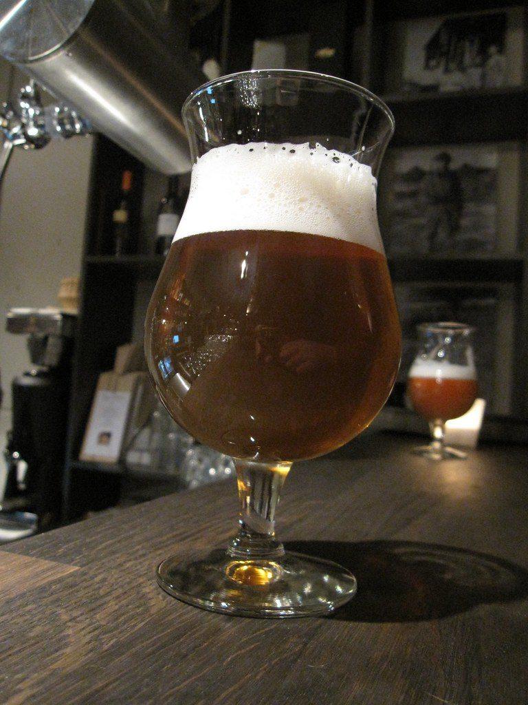 Une bière brune servie dans un verre tulipe